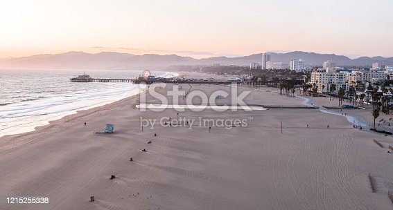 Aerial shot of the famous Santa Monica Beach and Pier, tourist attractions in Los Angeles California. The Pier and Beach have recently been completely closed to the public due to the Coronavirus pandemic of 2020.