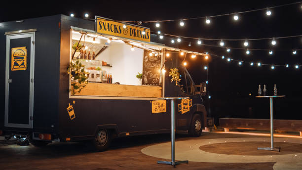 Empty Scene with a Dark Street Food Van Standing in the Evening in a Nice Warmly Lit Neighbourhood Next to the Sea. Food Truck Has Burgers and Drinks for Sale. Tables Have Bottles on Them. Empty Scene with a Dark Street Food Van Standing in the Evening in a Nice Warmly Lit Neighbourhood Next to the Sea. Food Truck Has Burgers and Drinks for Sale. Tables Have Bottles on Them. food truck stock pictures, royalty-free photos & images