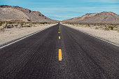 Empty scenic long straight desert road with yellow marking lines
