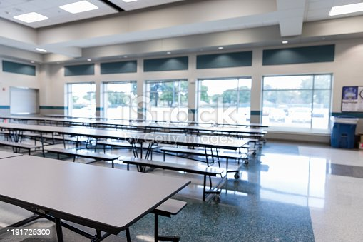 Clean, empty school cafeteria with large windows is ready for students.