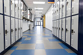 Empty hallway in middle school. Lockers line the walls. A door is at the end of the hall.