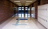 An empty school hallway lined with lockers.