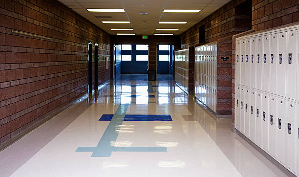 Empty School Hallway An empty school hallway lined with lockers. corridor stock pictures, royalty-free photos & images