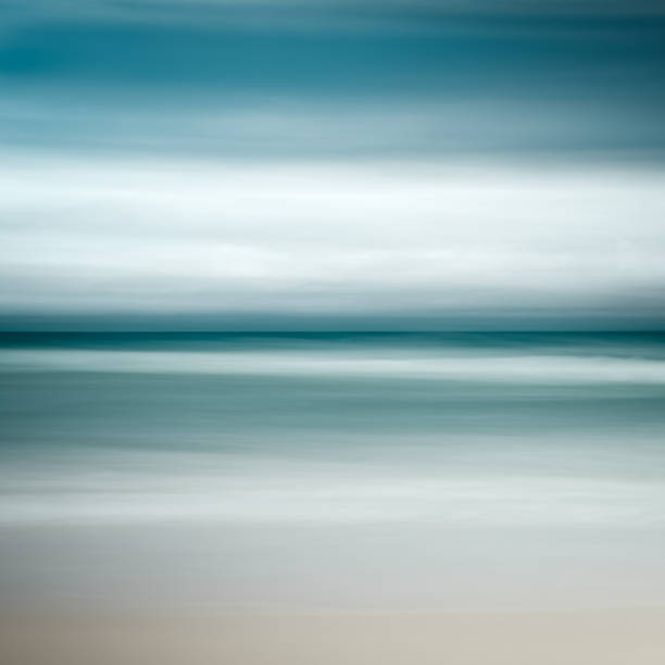Background Of Blurred Beach And Sea Waves With Bokeh: Coastal Abstract Motion Blurred Ocean Waves Blue Tones