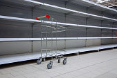 empty shelves and shopping cart in supermarket, all sold out due to panic caused by virus outbreak