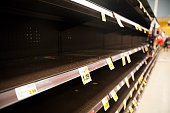 Empty shelves in a supermarket. Store is out of stock after panic buying.