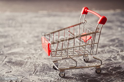 istock Empty shopping cart on gray background. Side view. 1183516507