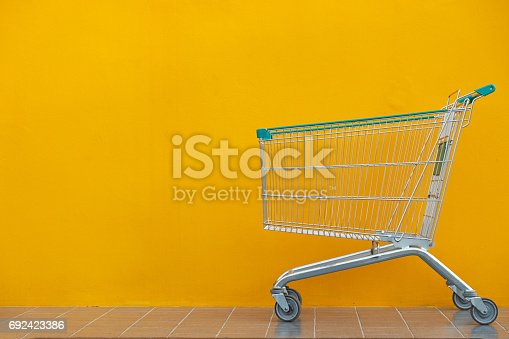 Empty shopping cart parking on yellow background with copyspace. retail store.