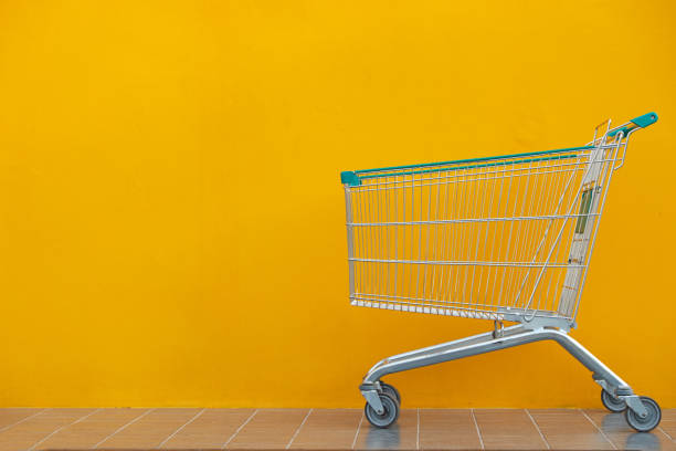 Empty shopping cart parking on yellow background with copyspace. stock photo