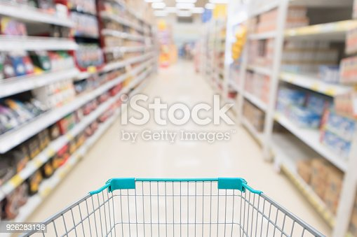istock Empty shopping cart with abstract blur supermarket discount store aisle and product shelves interior defocused background 926283136