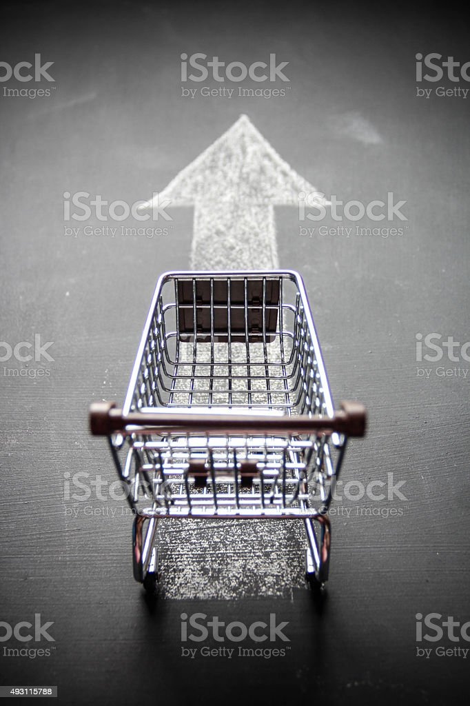 Empty shopping cart with arrow sign on blackboard stock photo