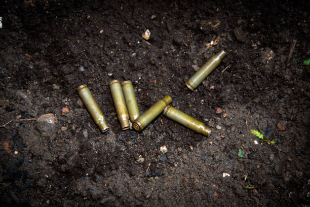empty shotgun shells from automatic weapons ammunition scattered on the ground empty shotgun shells from automatic weapons ammunition scattered on the ground mass murder stock pictures, royalty-free photos & images