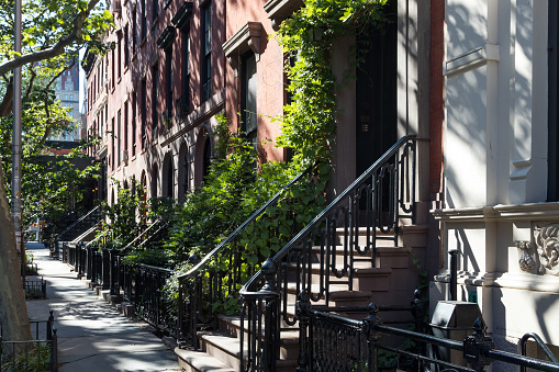 Empty sidewalk in front of historic brownstone buildings in the Gramercy Park neighborhood of Manhattan in New York City NYC