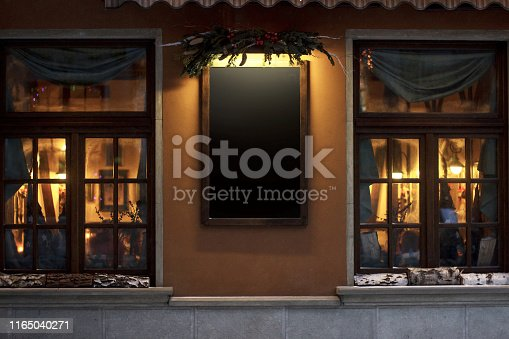 empty sign board for advertising text. christmas luxury decorated store front with garland lights in european city street at winter seasonal holidays. mock up