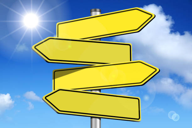 Empty signpost with four arrows stock photo