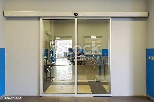 istock Empty sliding glass front door at the airport. Glass doors in the office. Glass entrance. Entrance to administration building equipped with automatic door 1180224653