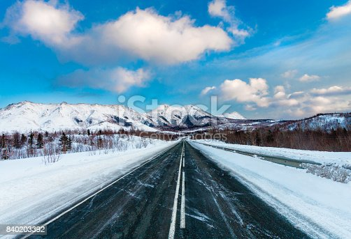 1066508460 istock photo Empty snow covered asphalt dark road with white road marking along mountains and hills and blue sky with clouds. Russia. Island Sakhalin 840203392