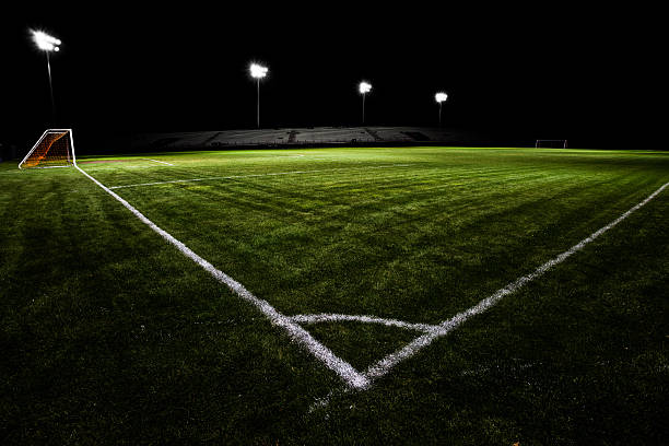 empty soccer field with floodlights at night - soccer field stock photos and pictures