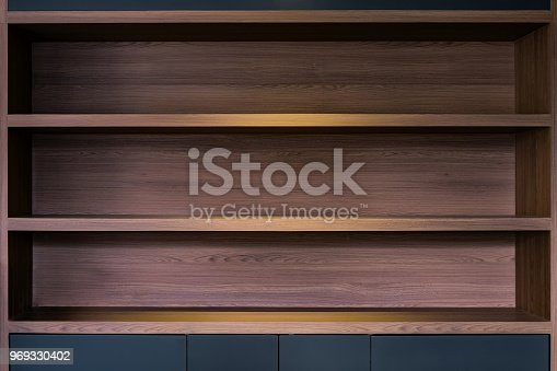 istock empty space of built in wooden shelf at wall with down-light 969330402