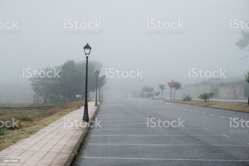Empty space outdoor asphalt parking lots in foggy morning stock photo
