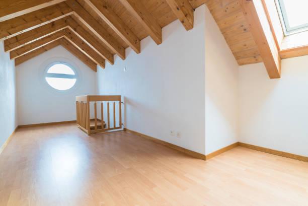geräumige und helle Dachboden in einer renovierten Wohnung mit Parkett Boden und weißen Wänden und hölzernen Satteldach – Foto