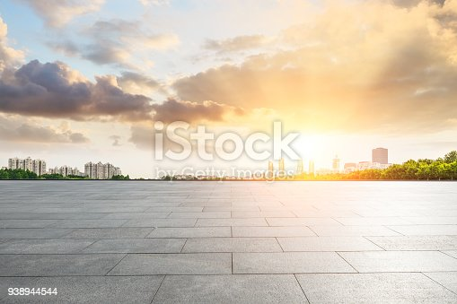 empty square floor and modern city scenery at sunset