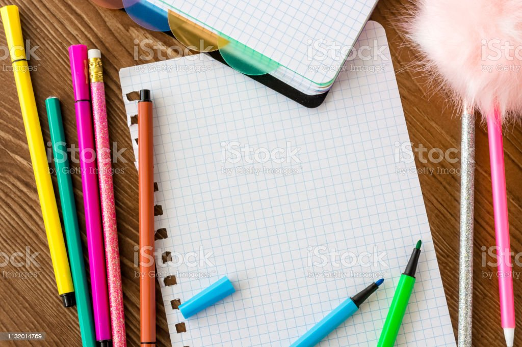 Empty squared page with open felt tip pens on wooden desk. stock photo