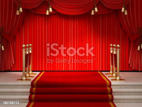 Red carpet and velvet ropes leading to the empty stage lit by spotlights.For more red carpet images: