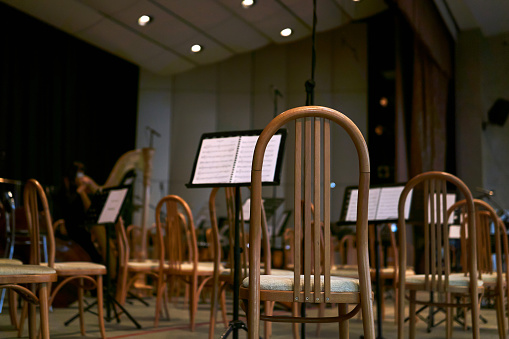 empty stage with chairs and musical scores before a symphony orchestra performance