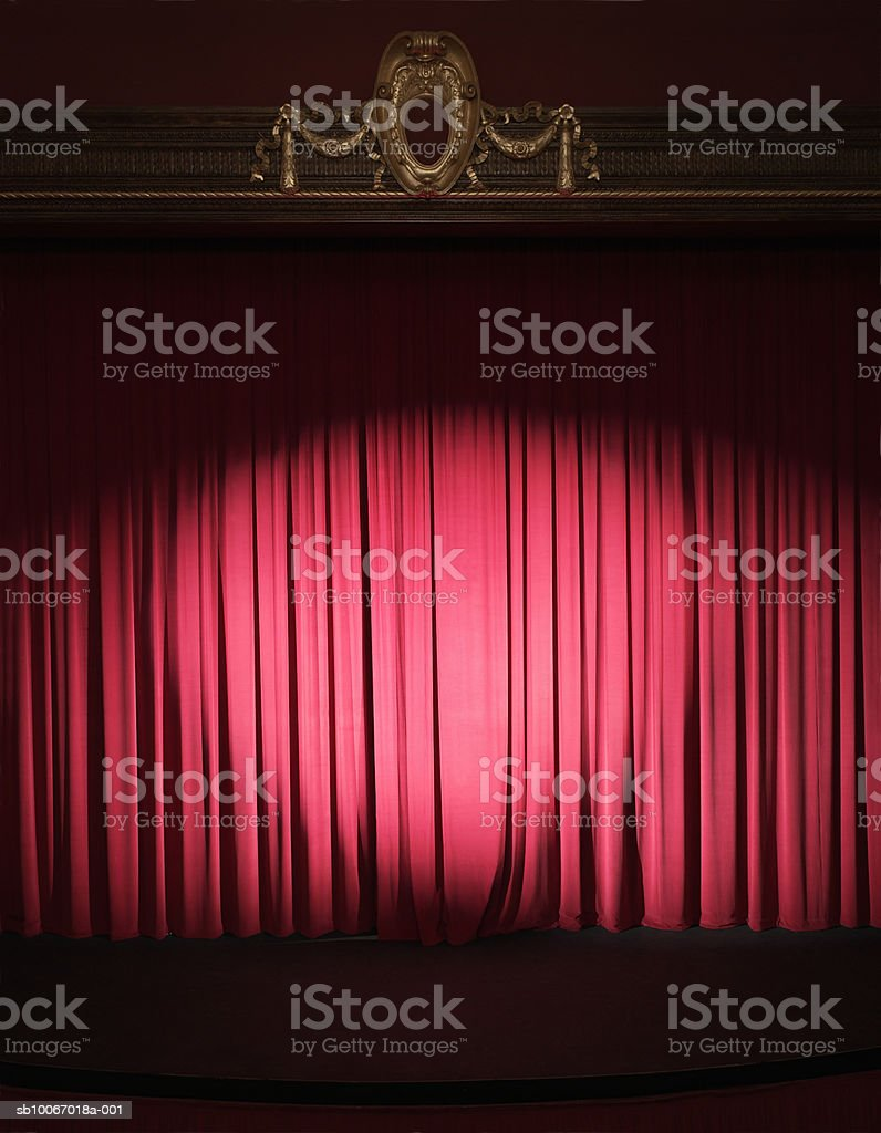 Empty stage with curtains closed and spotlight on royalty-free stock photo