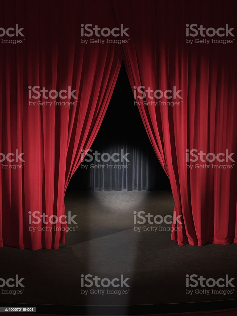 Empty stage with curtains slightly open and spotlight on royalty free stockfoto