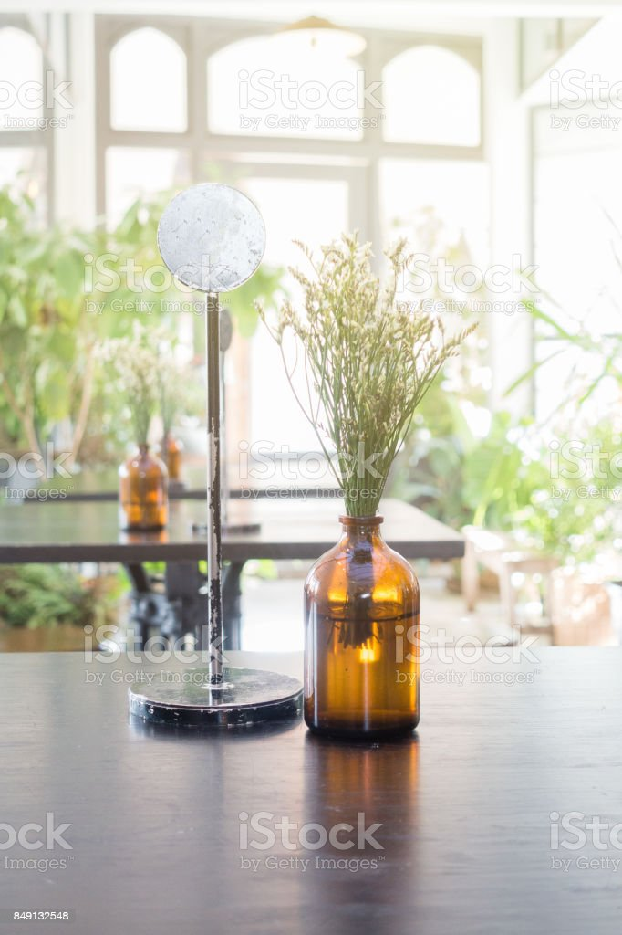 Empty steel label for table in restaurant with small flower vas. stock photo