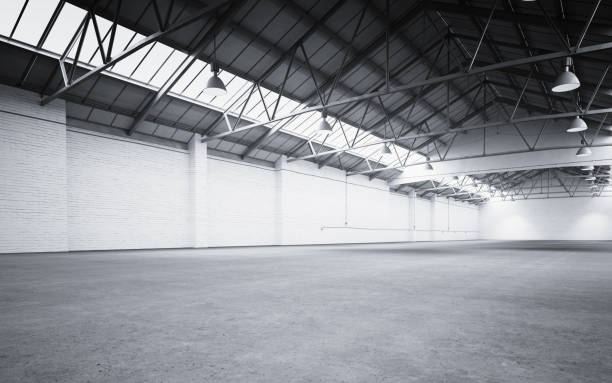 Empty storehouse interior Empty storehouse interior iluminated by spotlights and natural light from roof windows. 3D rendered image. warehouse interior stock pictures, royalty-free photos & images