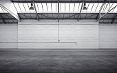 Empty storehouse interior iluminated by spotlights and natural light from roof windows.