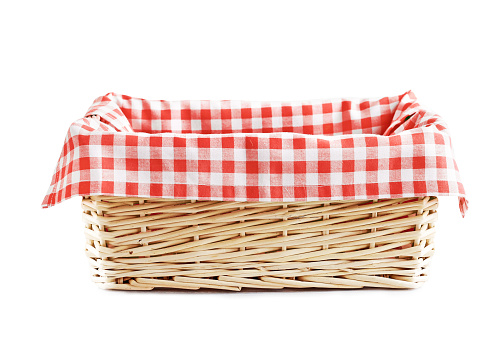 Empty straw basket with checkered red linen isolated.