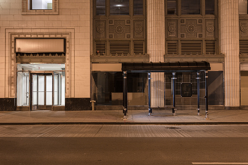 Empty street and bus stop vestibule at night in downtown Chicago