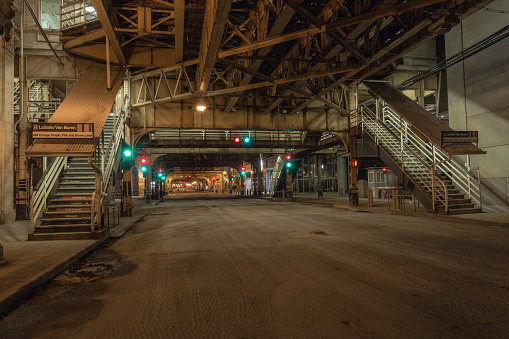Chicago, Illinois. USA - May 1, 2020: Empty street in downtown Chicago at night with train overpass and stairs