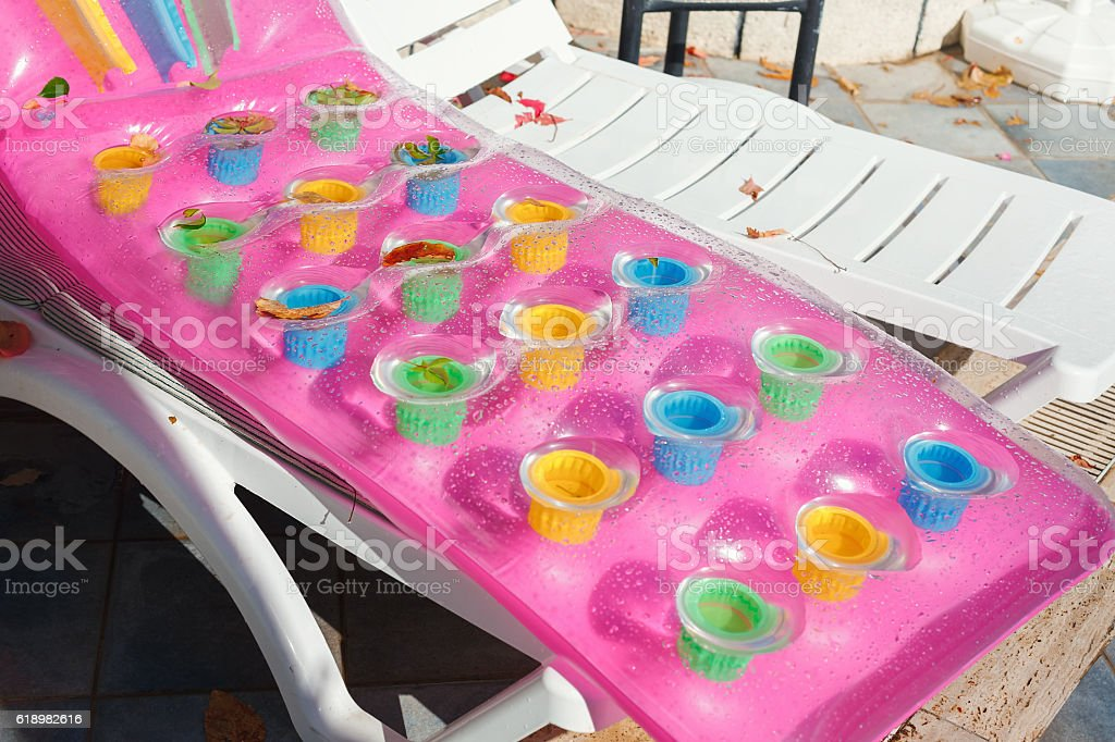 Empty sun beds with inflatable swimming mattress in the hotel stock photo