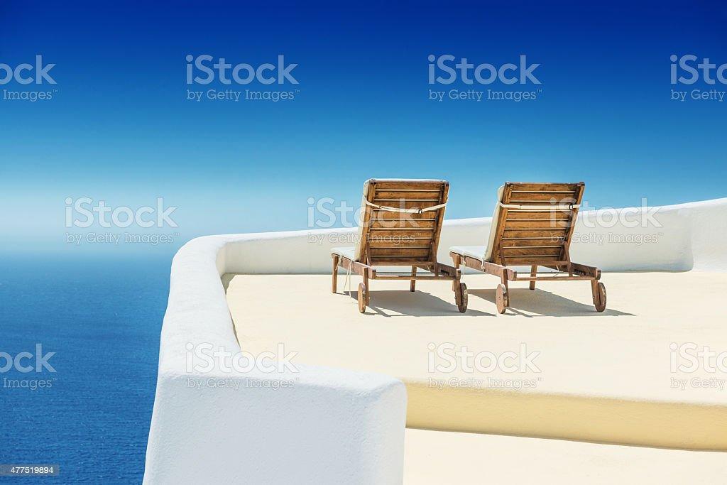 Empty Sun Lounge Chair on balcony In Santorini at Sunrise stock photo