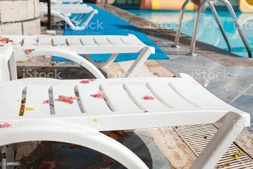 Empty sun loungers at the hotel with fallen leaves stock photo