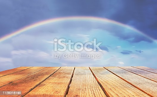 Empty surface of a wooden table on a background of a cloudy sky with a natural rainbow. Free place.