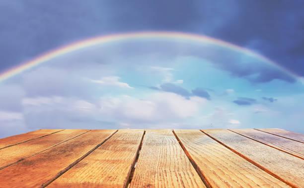 leere fläche an einem holztisch auf einem regenbogen-hintergrund - französische land tisch stock-fotos und bilder