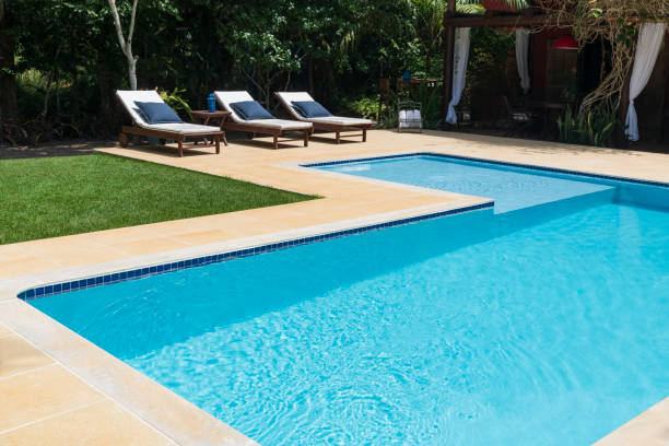Empty swimming pool with lounge chairs stock photo