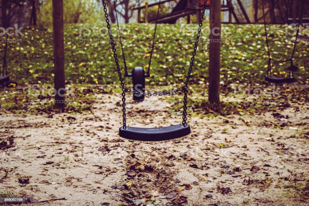 Empty swing at playground - missing child stock photo