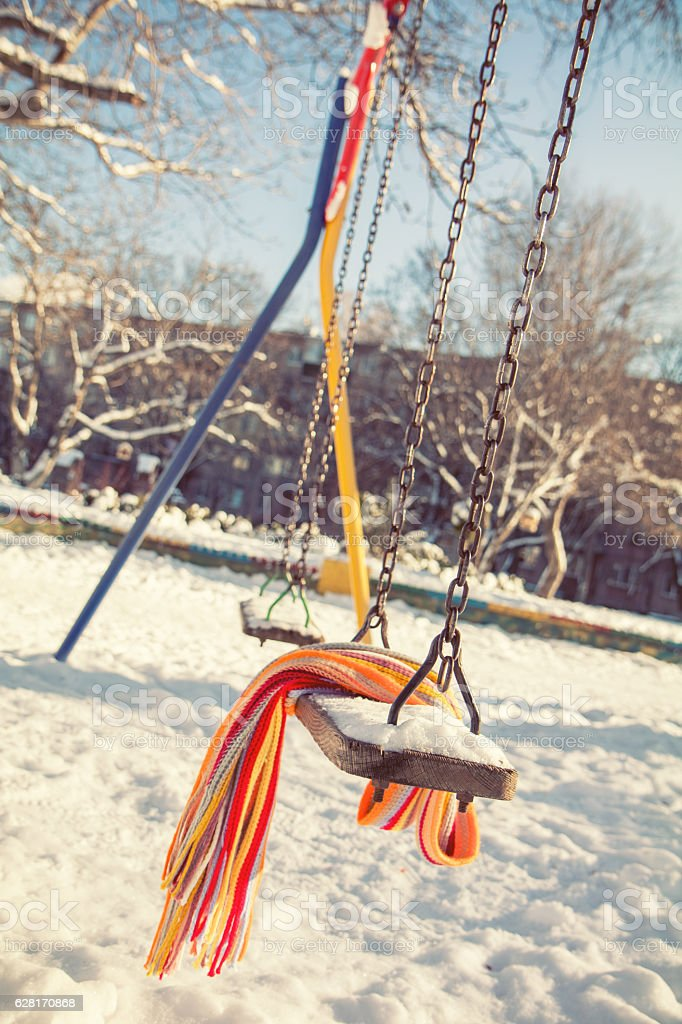 Empty swing with snow and checkered scarf royalty-free stock photo