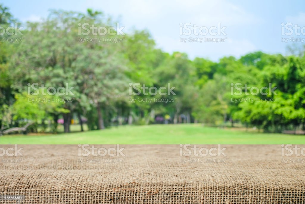 Empty table and sack tablecloth over blur park with bokeh background, for product display montage photo libre de droits