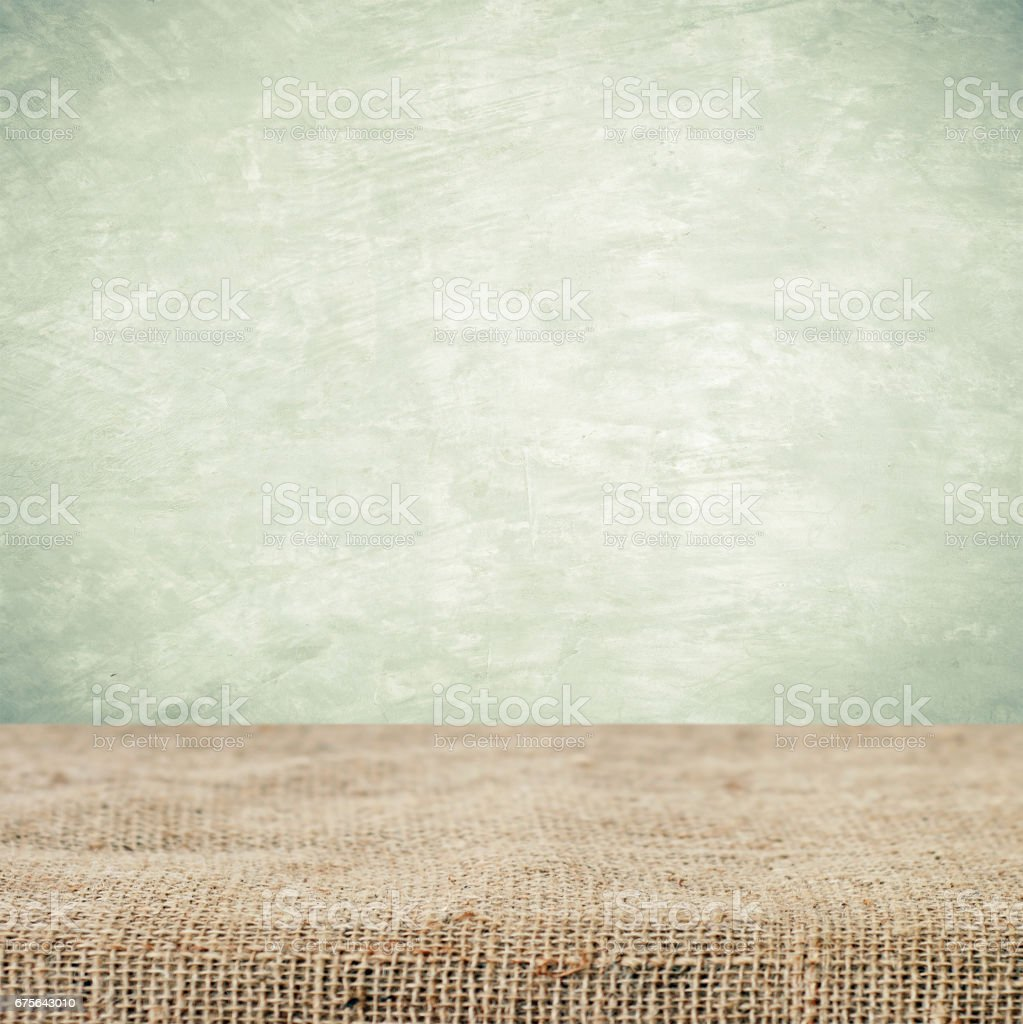Empty table and sack tablecloth over grunge cement wall background, product display montage, vintage style royalty-free stock photo