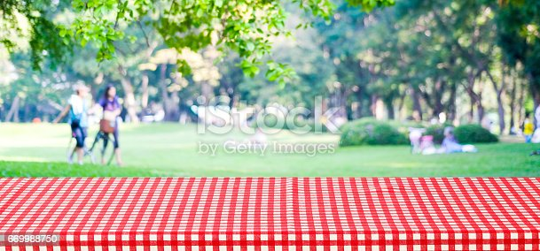 istock Empty table cover with red tablecloth over blur park with people background, for product display montage background, banner 669988750