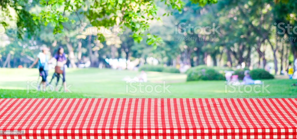 Empty table cover with red tablecloth over blur park with people background, for product display montage background, banner stock photo