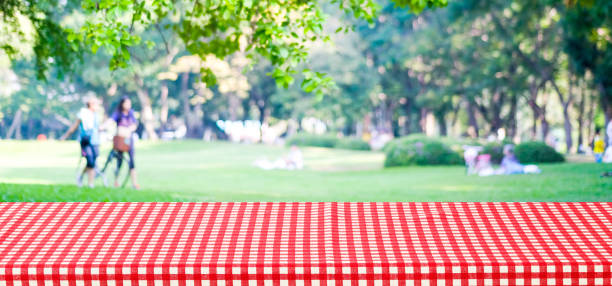 empty table cover with red tablecloth over blur park with people background, for product display montage background, banner - picnic foto e immagini stock
